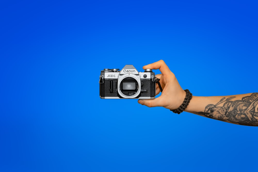 person holding silver and black dslr camera