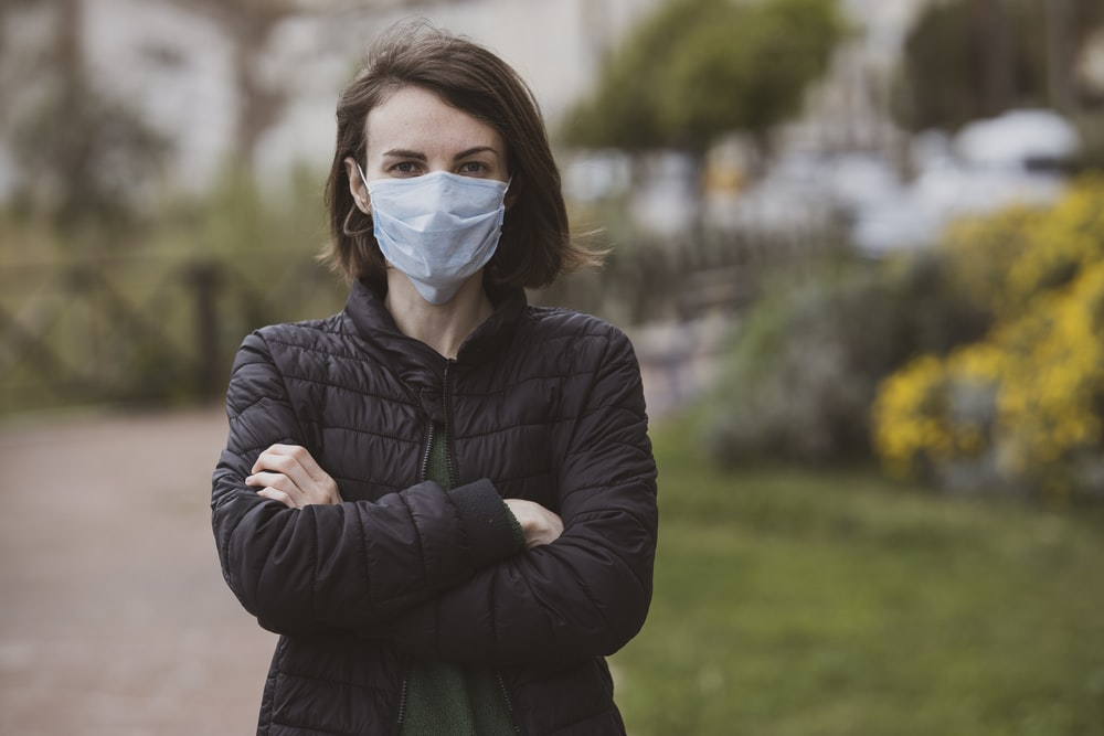 woman in black jacket wearing white mask