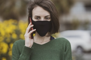 woman in green sweater holding black mask