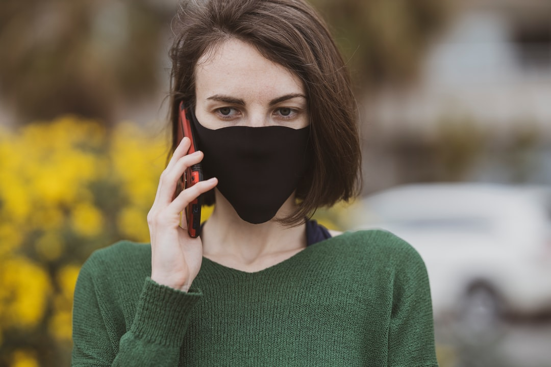 a woman talking on the phone with coronavirus mask