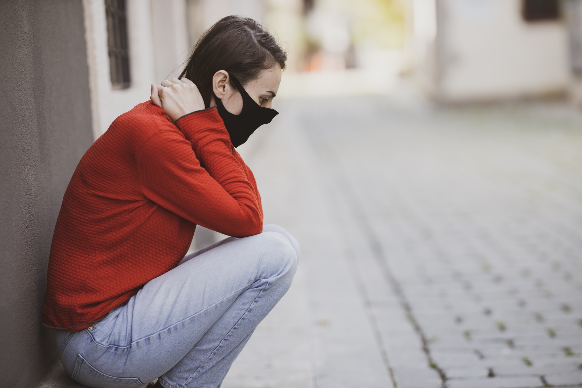 woman in red sweater and blue denim jeans sitting on concrete pavement