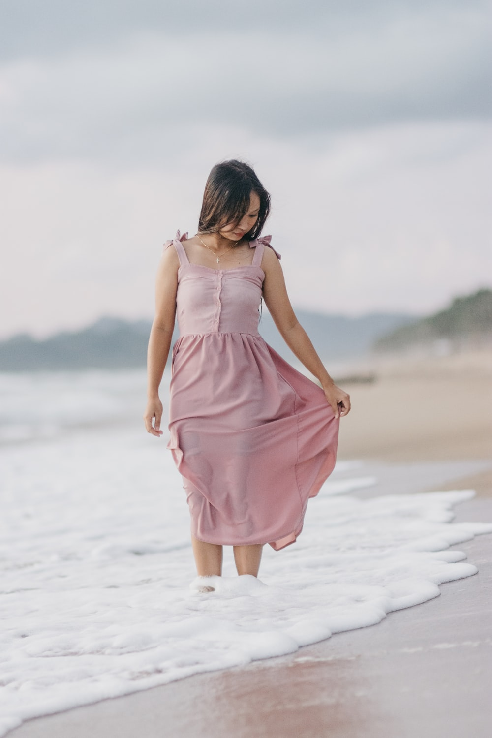 woman in pink sleeveless dress standing on beach during daytime