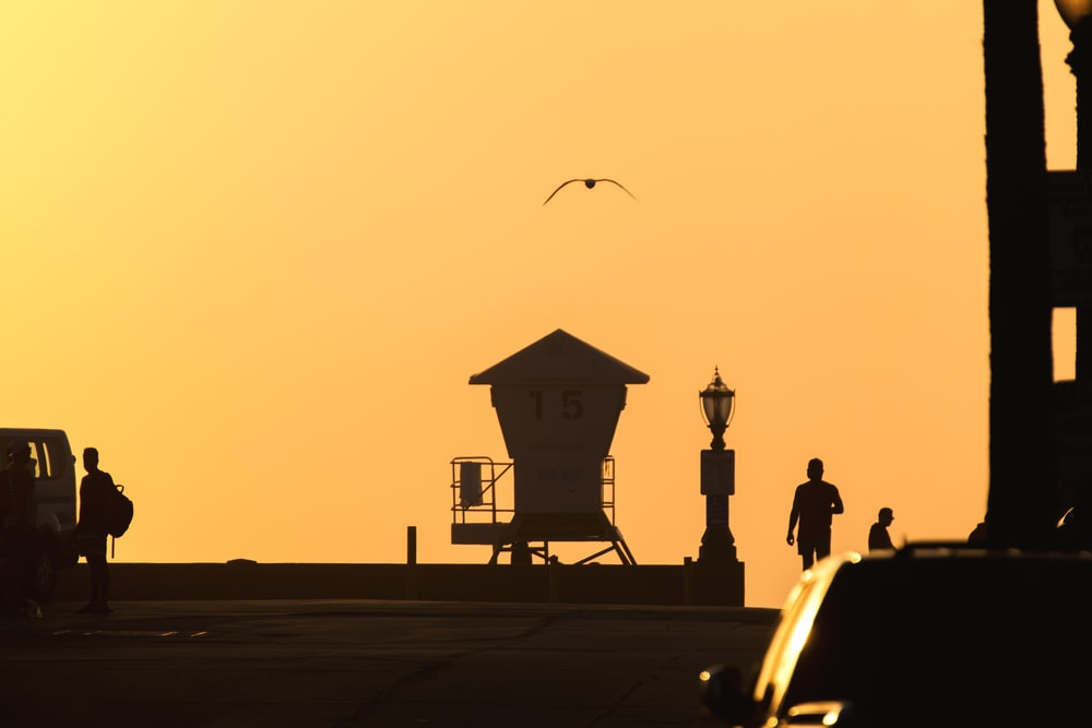 silhouette of people walking on street during sunset