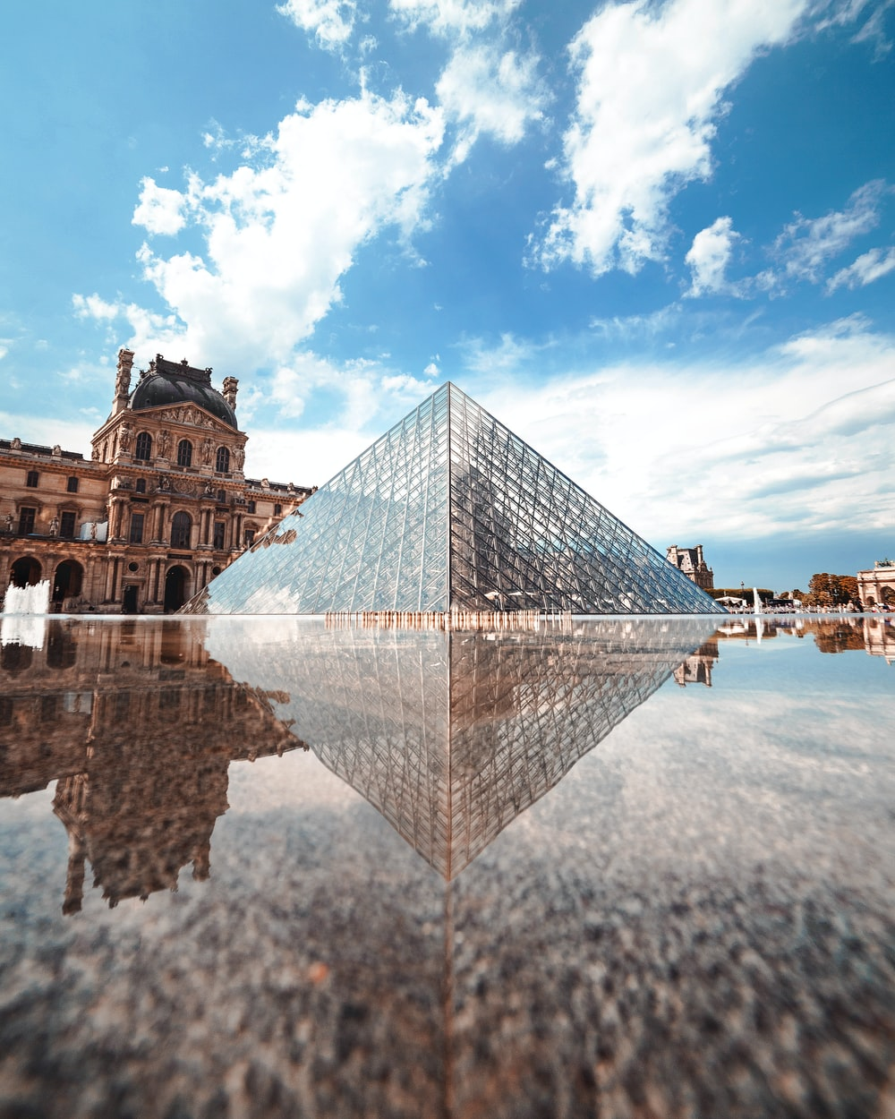 glass pyramid building near body of water during daytime
