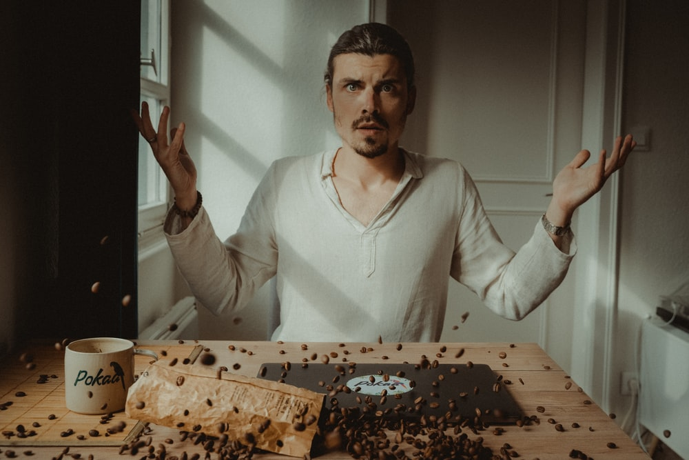 man in white v neck long sleeve shirt holding brown and black cake
