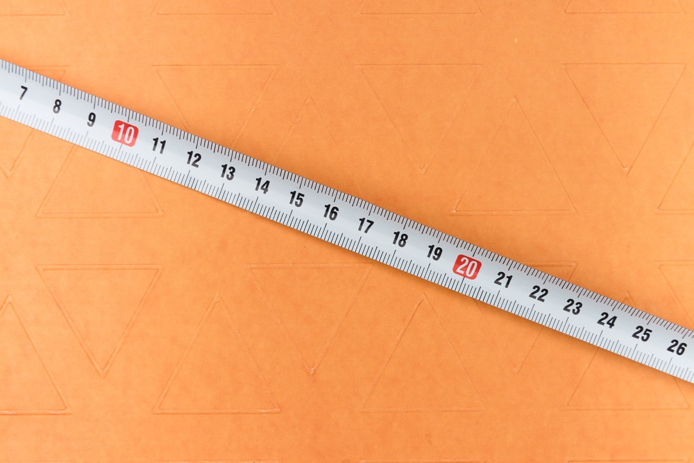 white and black ruler on brown surface