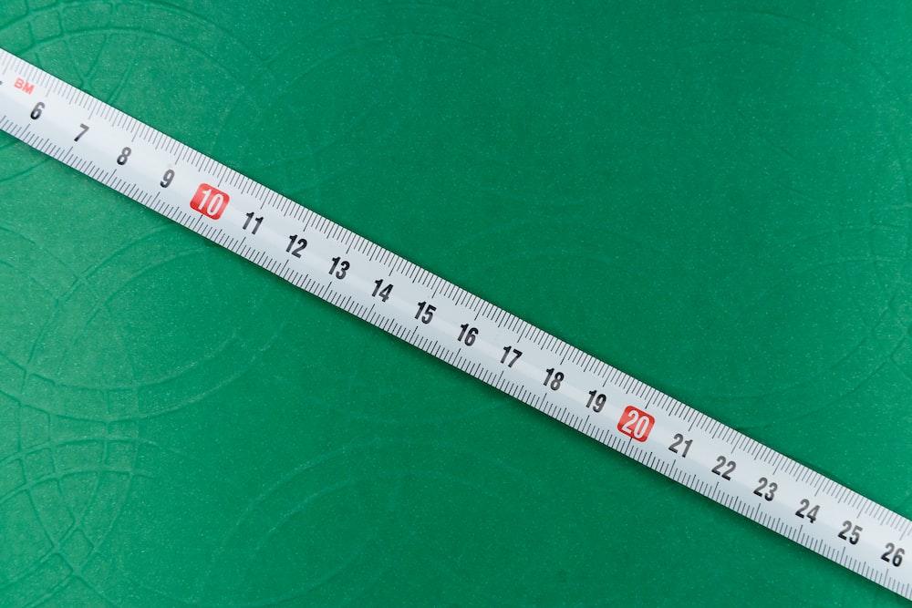 white ruler on green textile