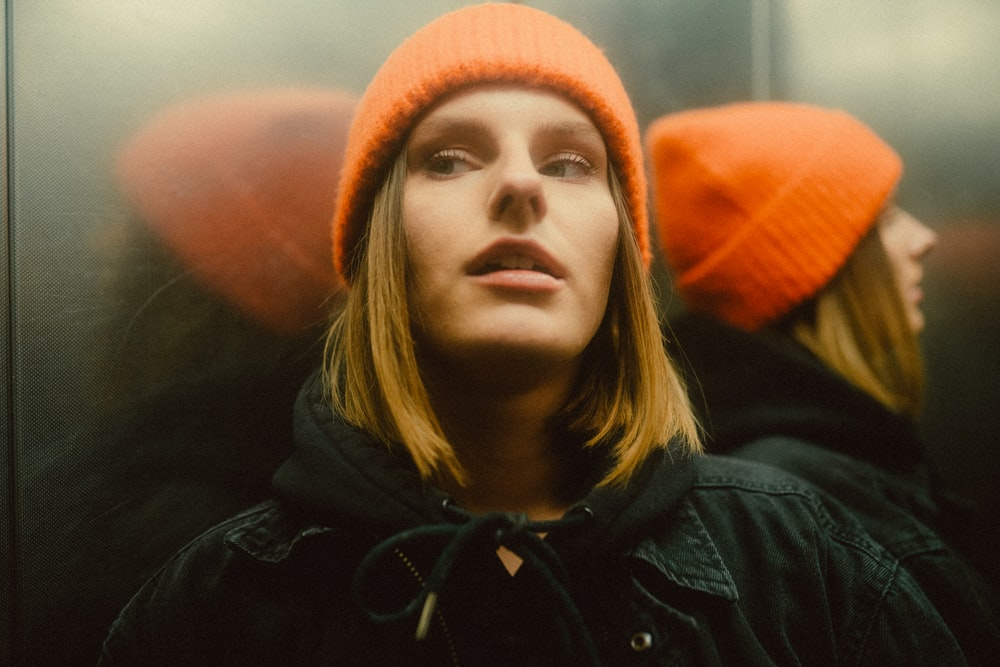 woman in black jacket and orange knit cap