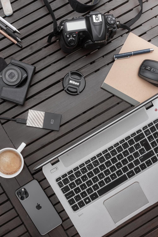black and silver headphones beside white apple keyboard and black headphones