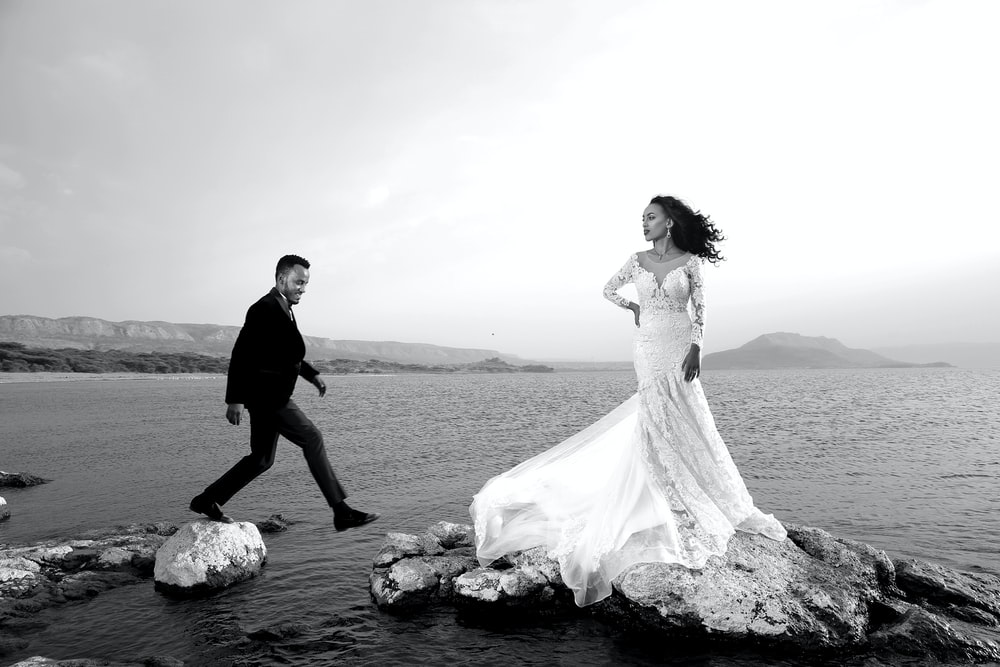 grayscale photo of bride and groom standing on rock near body of water