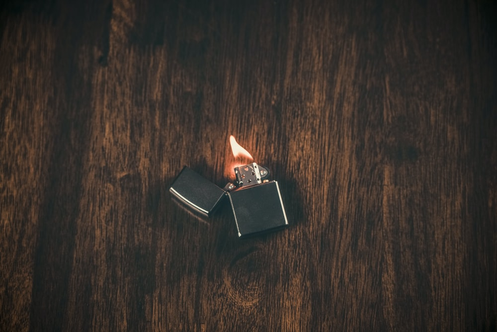 silver flip lighter on brown wooden table