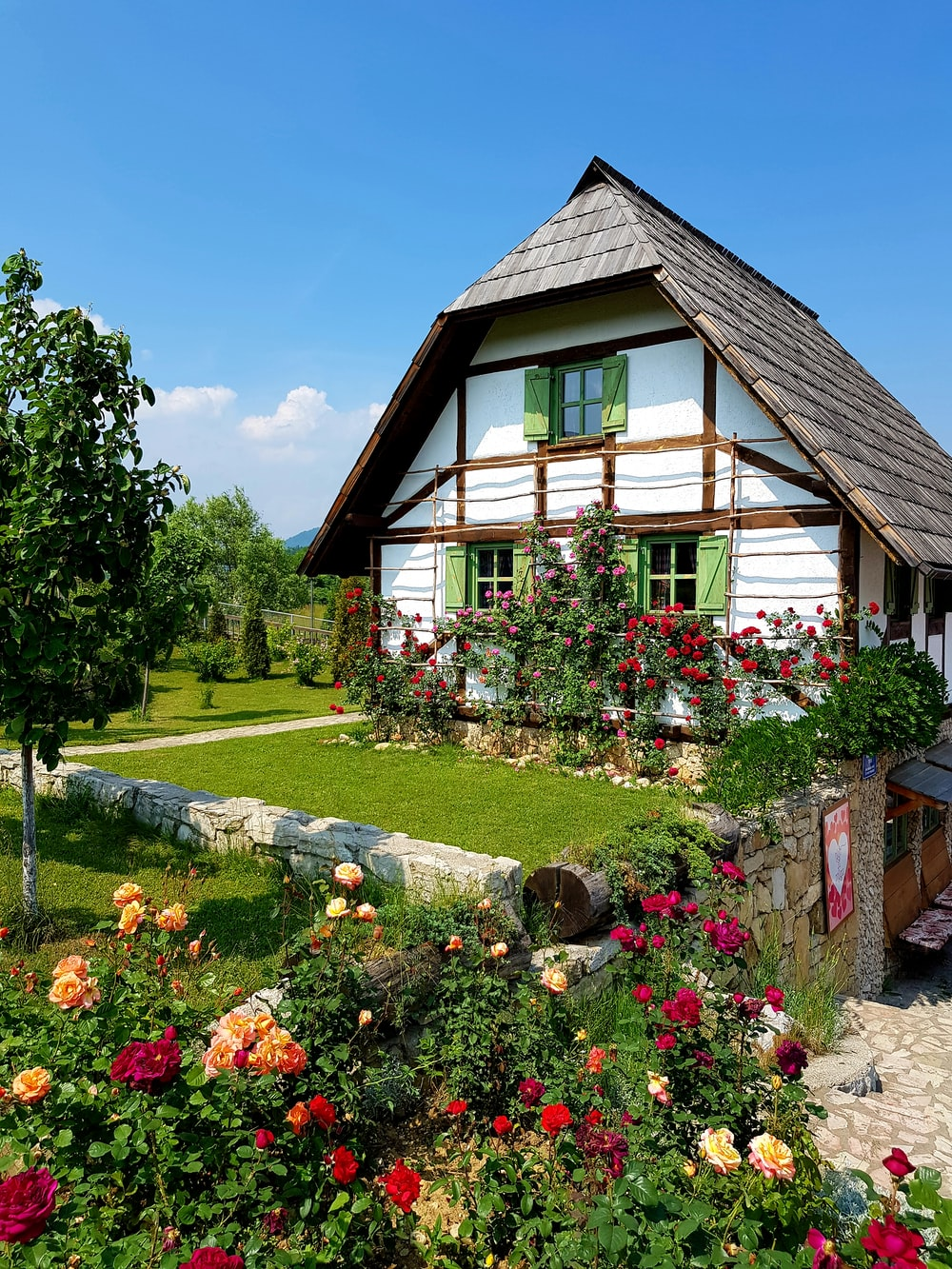 brown wooden house surrounded by green trees and flowers under blue sky during daytime