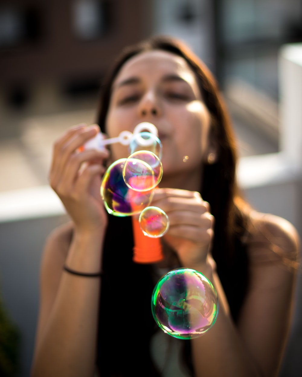 woman blowing bubbles during daytime