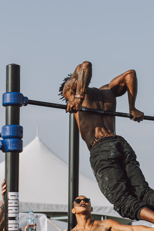 man in black pants climbing on brown wooden ladder during daytime
