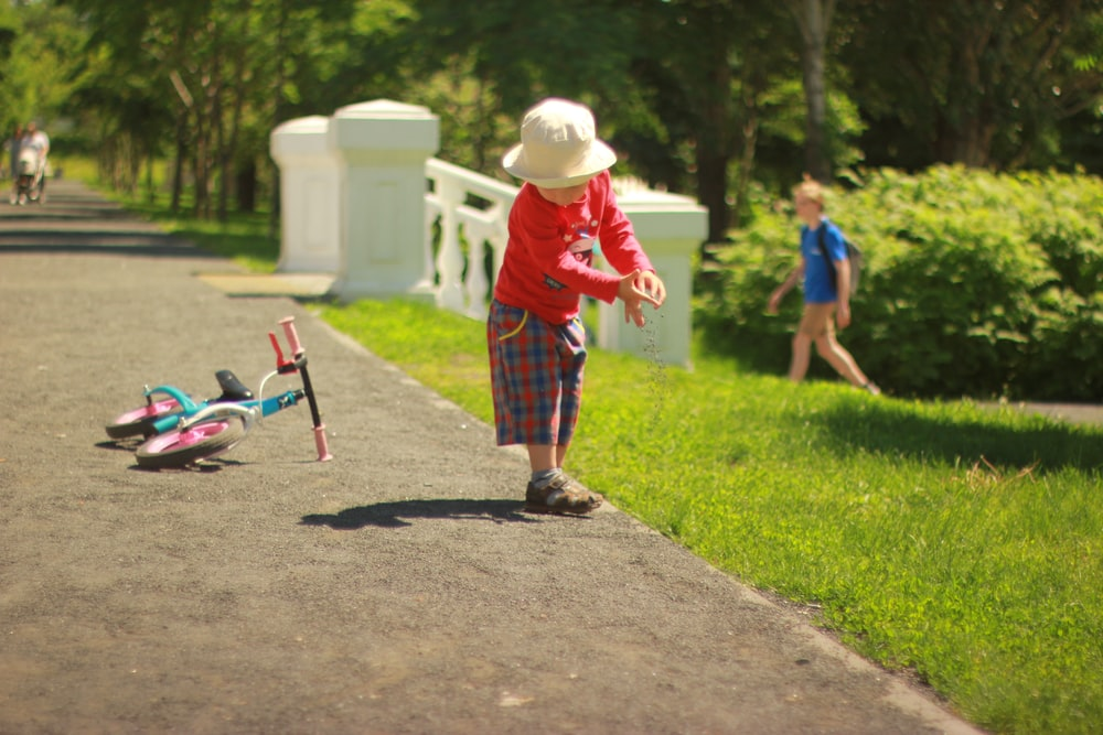 boy in red and white stripe shirt and blue pants walking on gray concrete pathway during