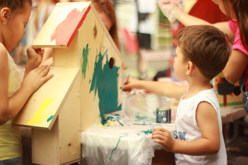 girl in white tank top holding blue and white paint brush
