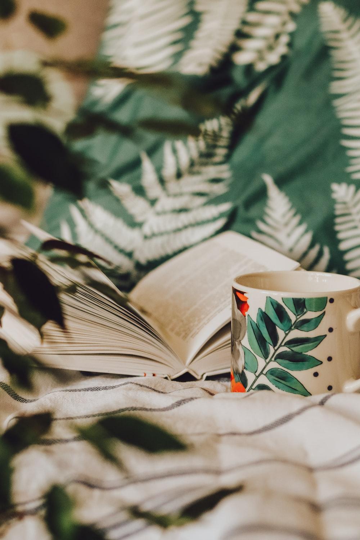 white and green floral ceramic mug on white paper