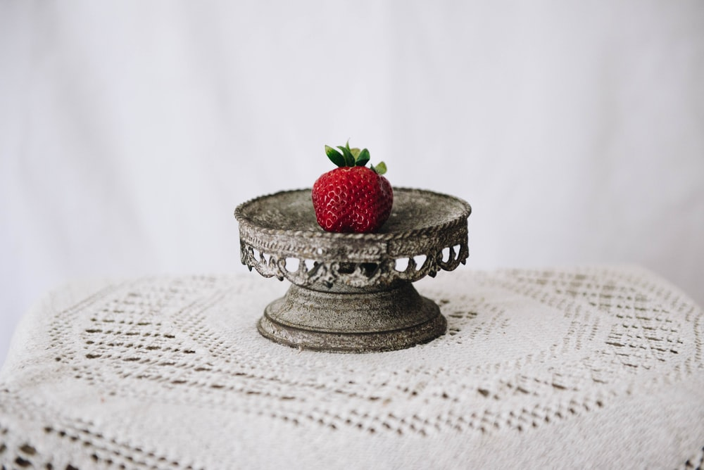 red strawberry on silver round tray