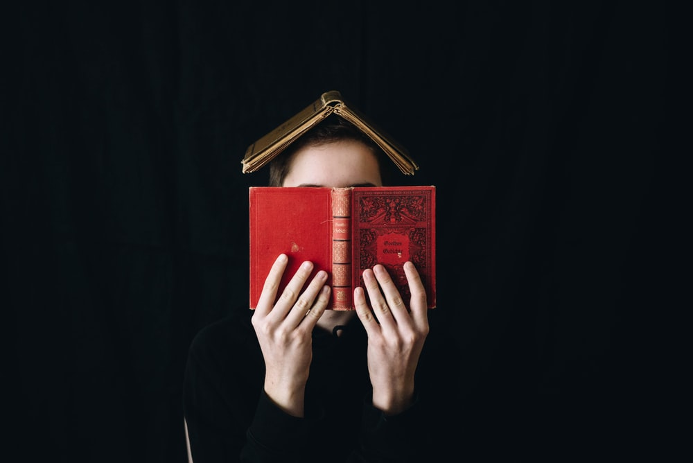 person holding red hardbound book