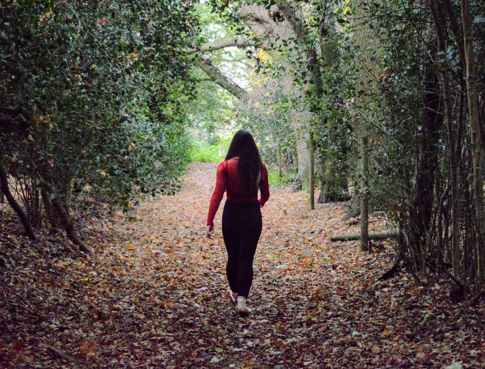 woman in red long sleeve shirt and black pants walking on forest during daytime