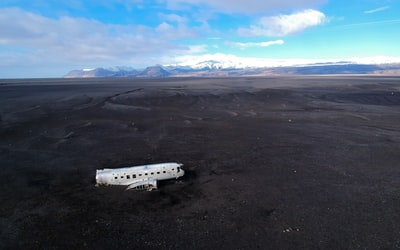 white airplane on gray sand during daytime space shuttle teams background