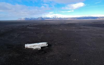 white airplane on gray sand during daytime spaceship zoom background