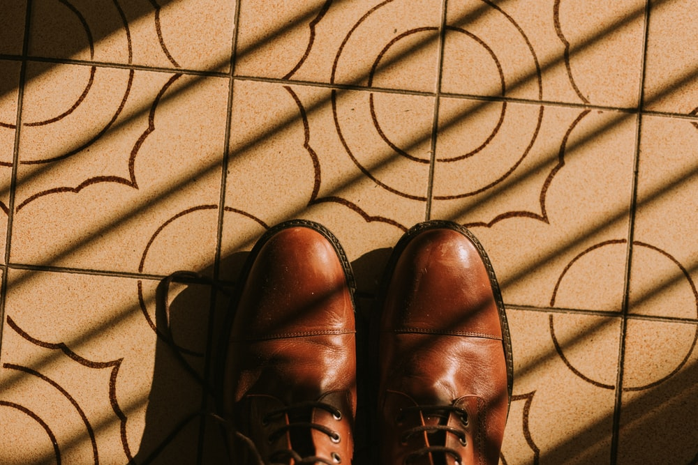 brown leather shoes on brown textile