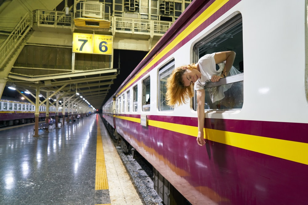 woman in white shirt standing beside train