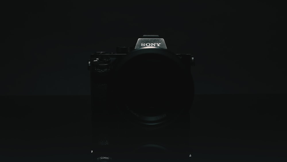 black nikon dslr camera on white surface
