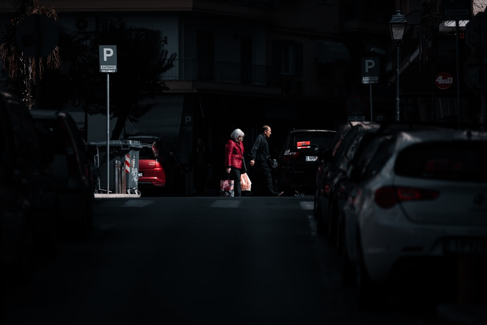 man in red jacket standing beside black car during night time