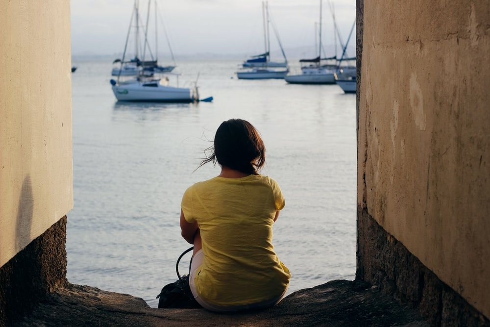 woman in yellow shirt sitting on brown wooden log near body of water during daytime
