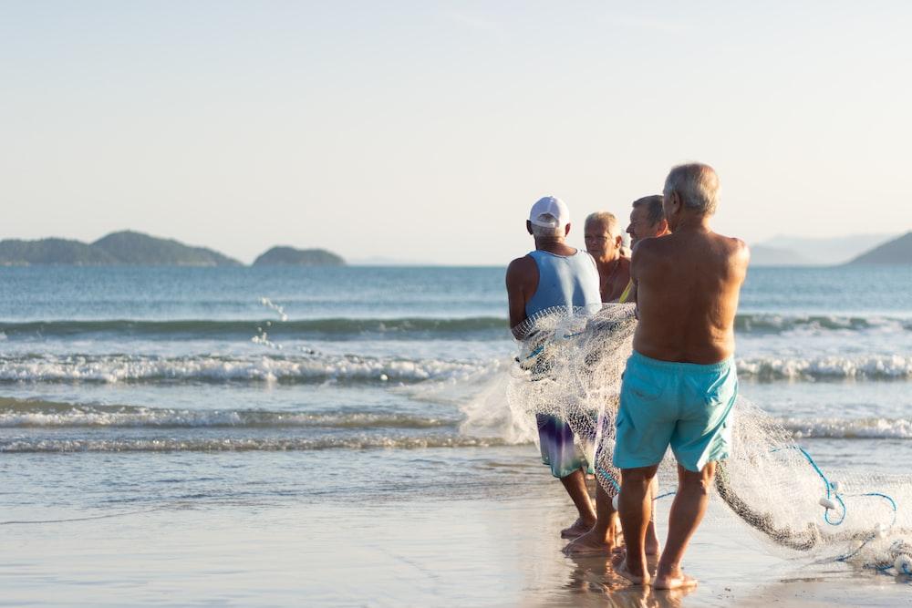 2 men in green shorts walking on beach during daytime