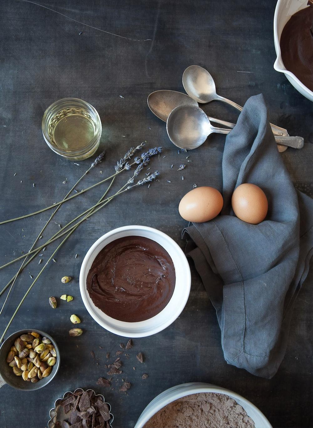 brown egg on white ceramic bowl beside stainless steel spoon