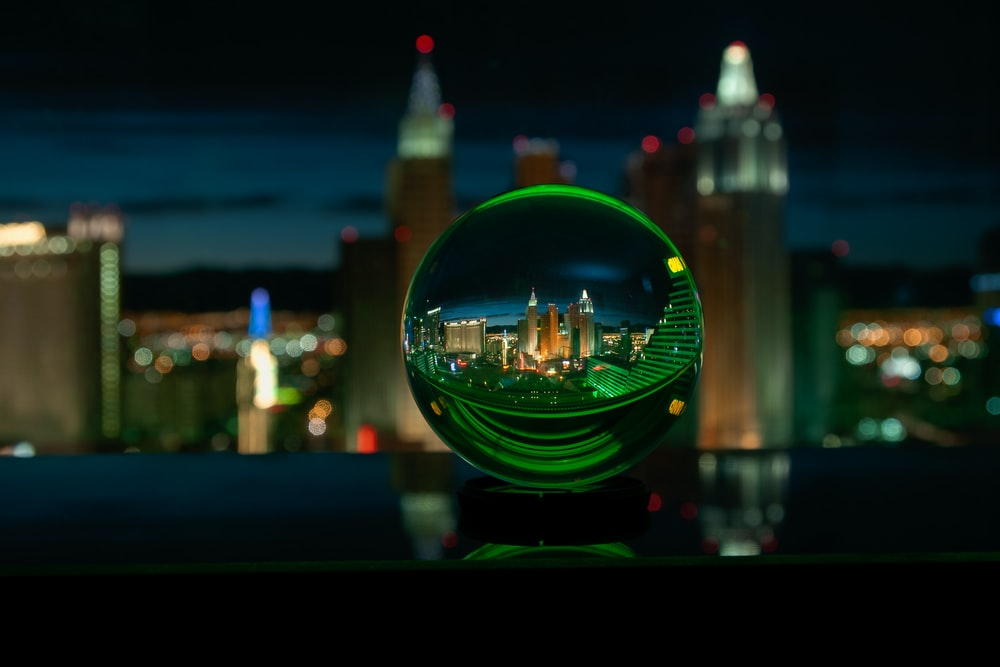 green glass ball with city lights during night time