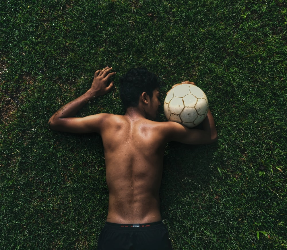 topless man lying on green grass field