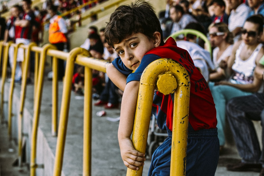 boy in blue and red shirt holding yellow metal bar