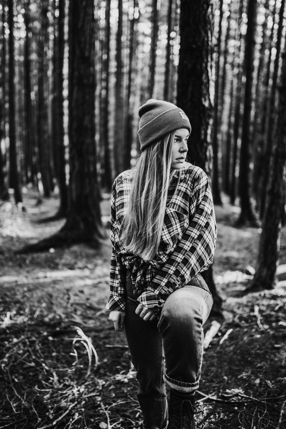 grayscale photo of woman in plaid shirt and denim jeans sitting on ground