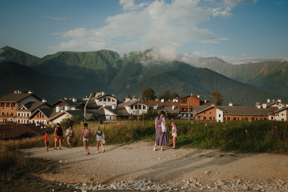 people walking on dirt road near houses and mountains during daytime