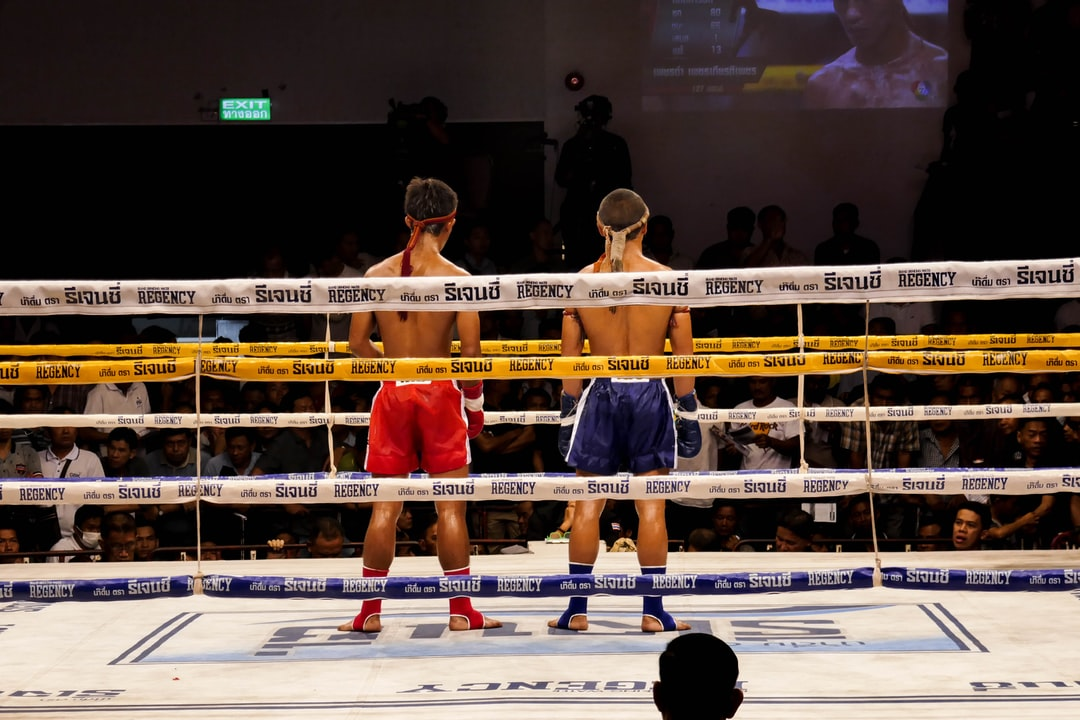 Two box thai fighter on a ring.