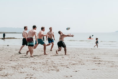 group of people playing beach volleyball on beach during daytime