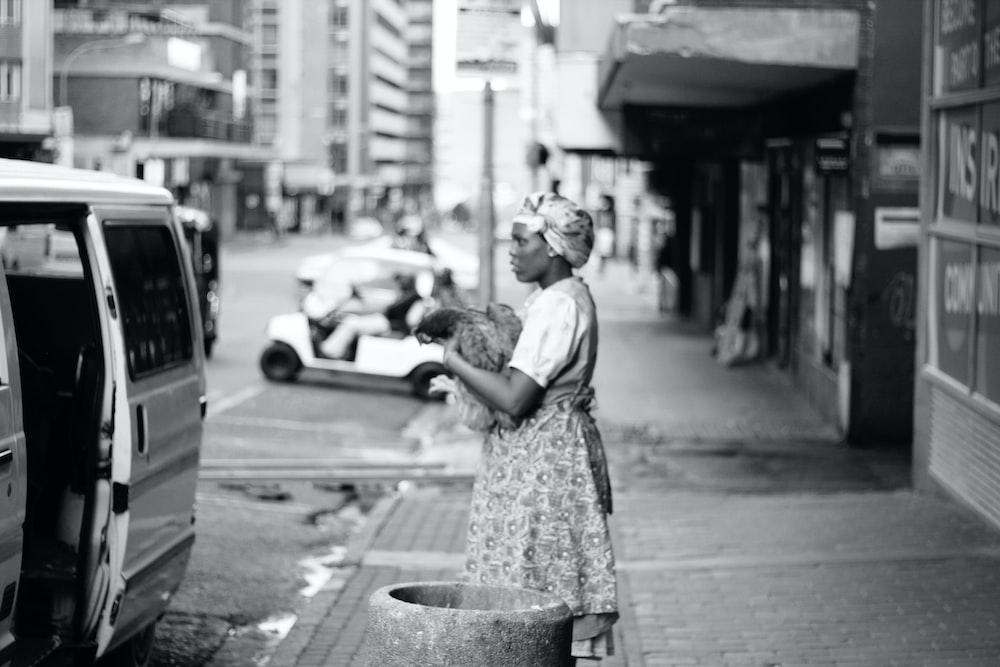 grayscale photo of woman in dress standing on sidewalk