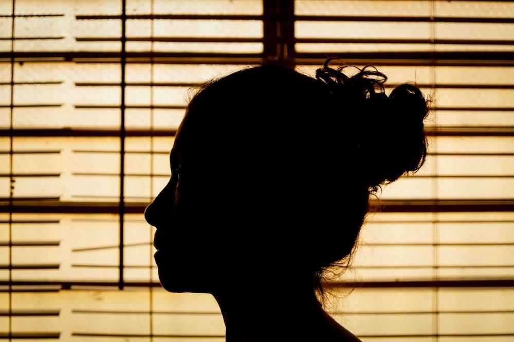 silhouette of woman near window blinds