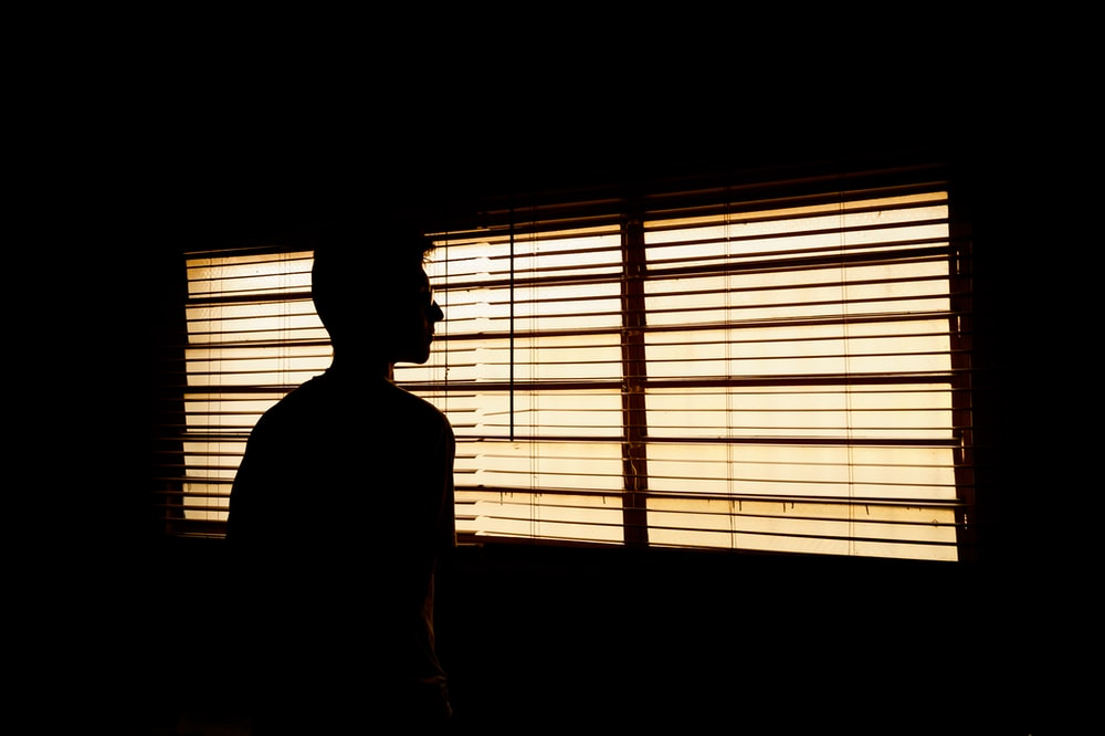 silhouette of person standing near window