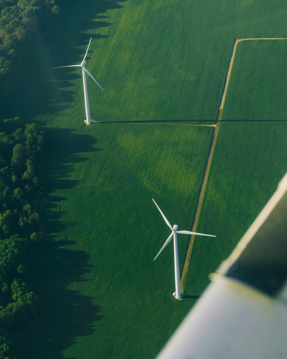 white wind turbines on green grass field during daytime