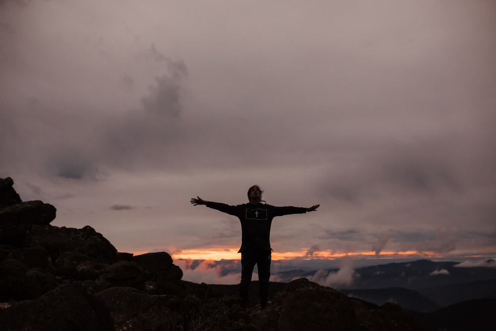 man standing on rock formation under cloudy sky during daytime
