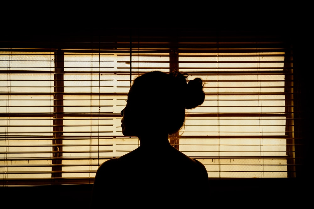 silhouette of woman standing near window blinds