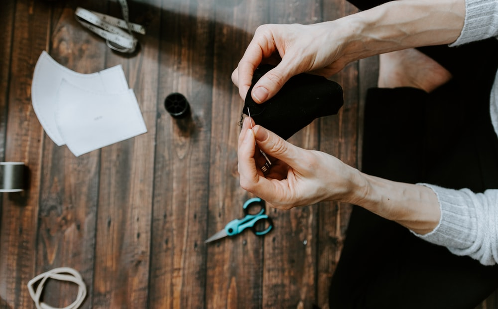 person holding blue and black scissors