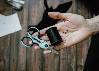 person holding black thread spool and silver scissors