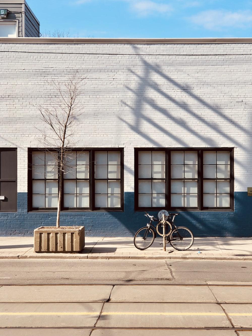 black bicycle parked beside blue concrete building