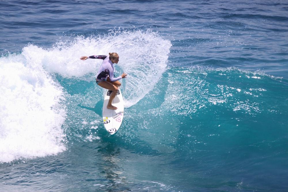 woman in black bikini surfing on sea waves during daytime